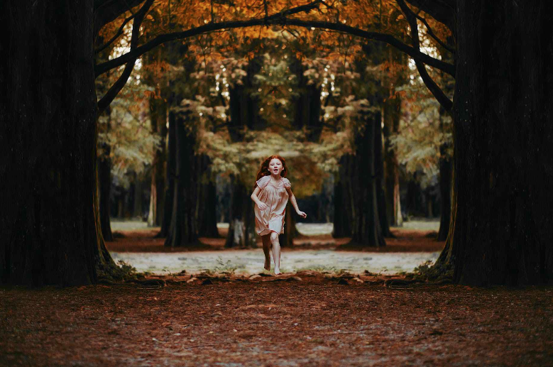 Photo by Matheus Bertelli- bambina corre nel bosco in autunno