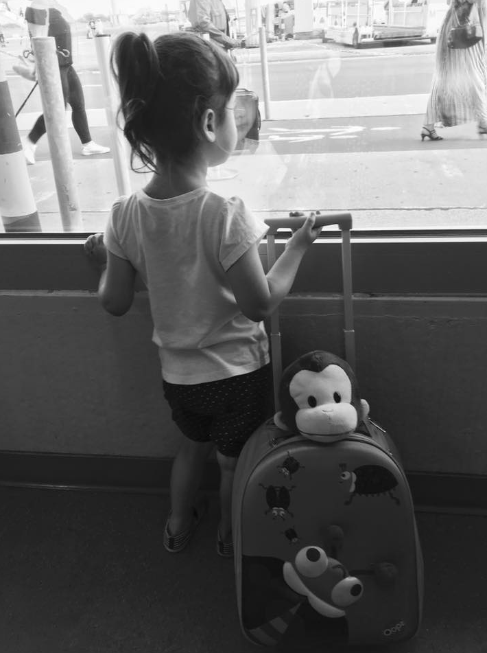 bambina in aeroporto con valigia